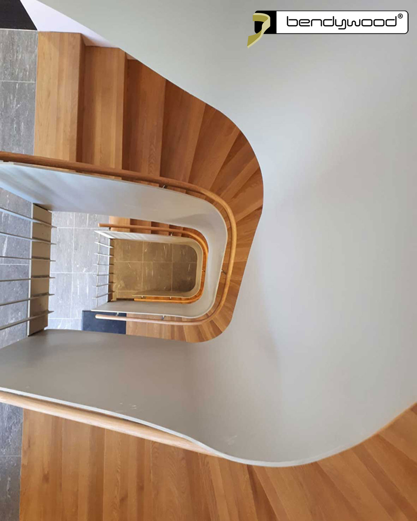 Round bending handrails in Bendywood®-oak fitted on a 10 mm thick curved steel plate stair railing.