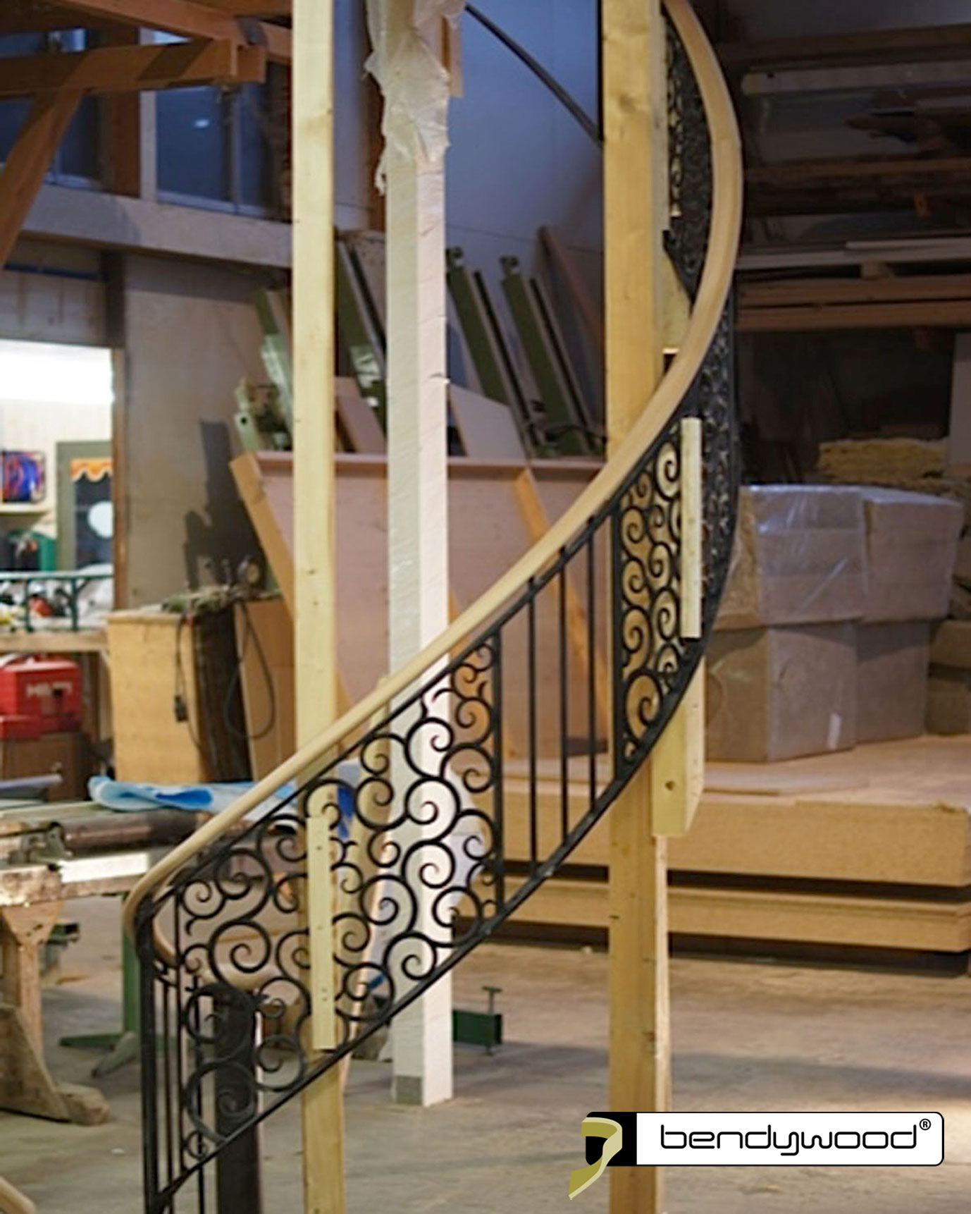 Oval bending handrail in Bendywood®-beech for curved staircase with wrought iron banister.