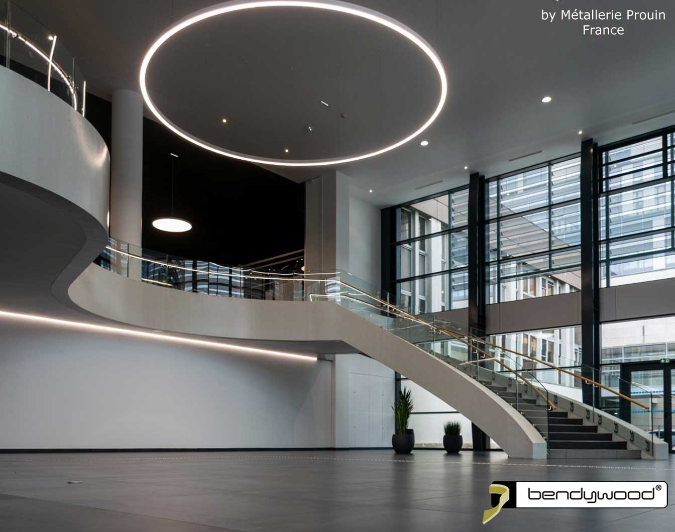 Bending wood Bendywood® - curved staircase with glass railing and wooden handrails with LED strip